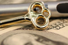 Finance concept. Image of key, pen and $100 dollar banknote Stock Photo