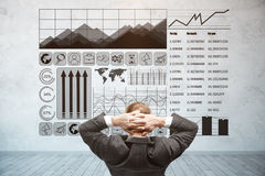 Finance concept. Back view of relaxing young businessman looking at concrete wall with business charts. Finance concept Royalty Free Stock Photo