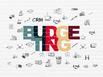 Finance concept: Budgeting on wall background. Finance concept: Painted multicolor text Budgeting on White Brick wall background with  Hand Drawn Business Icons Royalty Free Stock Photo
