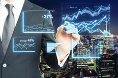 Finance concept. Closeup of businessman's hand drawing digital business charts on night city background. Finance concept Stock Photography