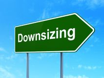 Finance concept: Downsizing on road sign background. Finance concept: Downsizing on green road highway sign, clear blue sky background, 3D rendering Stock Photography