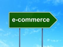 Finance concept: E-commerce on road sign background. Finance concept: E-commerce on green road highway sign, clear blue sky background, 3D rendering Royalty Free Stock Photography