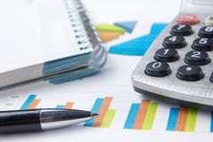Finance concept - Financial accounting stock. Market graphs analysis. Calculator, notebook with blank sheet of paper, pen on chart. Top view Royalty Free Stock Photos