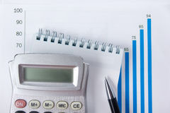 Finance concept - Financial accounting stock. Market graphs analysis. Calculator, notebook with blank sheet of paper, pen on chart. Top view Royalty Free Stock Images