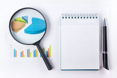 Finance concept - Financial accounting stock. Market graphs analysis. Magnifying glass, notebook with blank sheet of paper, pen on chart. Top view stock images