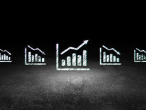 Finance concept: growth graph icon in grunge dark. Finance concept: row of Glowing decline graph icons around growth graph icon in grunge dark room Dirty Floor Royalty Free Stock Images