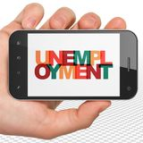 Finance concept: Hand Holding Smartphone with Unemployment on  display. Finance concept: Hand Holding Smartphone with Painted multicolor text Unemployment on Royalty Free Stock Images