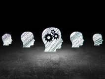 Finance concept: head with gears icon in grunge. Finance concept: row of Glowing head icons around head with gears icon in grunge dark room Dirty Floor, dark Stock Image