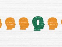 Finance concept: head with keyhole icon on wall. Finance concept: row of Painted orange head icons around green head with keyhole icon on White Brick wall Royalty Free Stock Image