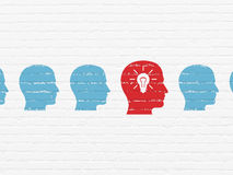 Finance concept: head with light bulb icon on wall. Finance concept: row of Painted blue head icons around red head with light bulb icon on White Brick wall Royalty Free Stock Images