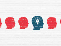 Finance concept: head with light bulb icon on wall. Finance concept: row of Painted red head icons around blue head with light bulb icon on White Brick wall Royalty Free Stock Image