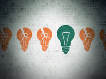 Finance concept: light bulb icon on Digital Paper background. Finance concept: row of Painted orange light bulb icons around green light bulb icon on Digital Royalty Free Stock Images
