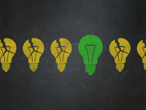 Finance concept: light bulb icon on School Board. Finance concept: row of Painted yellow light bulb icons around green light bulb icon on School Board background Stock Photography