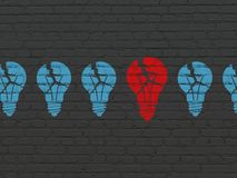 Finance concept: light bulb icon on wall background. Finance concept: row of Painted blue light bulb icons around red light bulb icon on Black Brick wall Stock Images