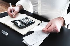 Man at desk with calculator, bills or sales slips and notpad. Finance concept with man at desk with calculator, bills or sales slips and notpad stock photography