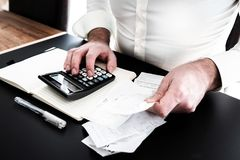 Man at desk with calculator, bills or sales slips and notpad. Finance concept with man at desk with calculator, bills or sales slips and notpad stock images