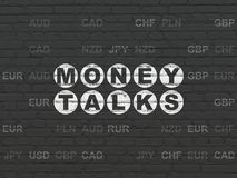Finance concept: Money Talks on wall background. Finance concept: Painted white text Money Talks on Black Brick wall background with Currency Royalty Free Stock Photography