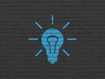 Finance concept: Light Bulb on wall background. Finance concept: Painted blue Light Bulb icon on Black Brick wall background Stock Photos