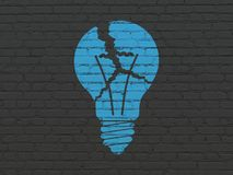 Finance concept: Light Bulb on wall background. Finance concept: Painted blue Light Bulb icon on Black Brick wall background Royalty Free Stock Image