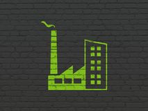 Finance concept: Industry Building on wall background. Finance concept: Painted green Industry Building icon on Black Brick wall background Stock Images
