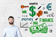 Finance concept. Portrait of attractive caucasian guy on brick background with colorful financial sketch. Finance concept Royalty Free Stock Image