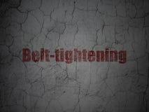 Finance concept: Belt-tightening on grunge wall background. Finance concept: Red Belt-tightening on grunge textured concrete wall background Royalty Free Stock Photos