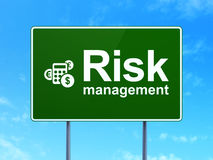 Finance concept: Risk Management and Calculator on. Finance concept: Risk Management and Calculator icon on green road (highway) sign, clear blue sky background Stock Photography