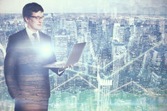 Finance concept. Side view of attractive young businessman using laptop on forex city background. Finance concept. Double exposure Stock Photo
