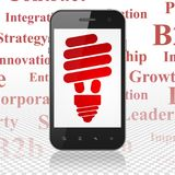 Finance concept: Smartphone with Energy Saving Lamp on display. Finance concept: Smartphone with  red Energy Saving Lamp icon on display,  Tag Cloud background Stock Image
