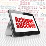 Finance concept: Tablet Computer with Achieve Success on display. Finance concept: Tablet Computer with  red text Achieve Success on display,  Tag Cloud Royalty Free Stock Photos