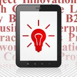 Finance concept: Tablet Computer with Light Bulb on display. Finance concept: Tablet Computer with  red Light Bulb icon on display,  Tag Cloud background, 3D Royalty Free Stock Photography