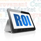 Finance concept: Tablet Computer with ROI on display. Finance concept: Tablet Computer with  blue text ROI on display,  Tag Cloud background, 3D rendering Stock Photos