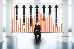 Finance concept. Thoughtful young businessman sitting in the middle of concrete interior with business chart and city view. Finance concept. 3D Rendering Stock Image