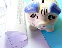 Finance documents. Ceramic piggy bank and finance documents on blue desk royalty free stock images