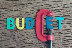Finance, economy and business squeezing idea, colorful alphabet. Of the word BUDGET using red clamp as G letter on wooden table, crisis and depression of Royalty Free Stock Photo