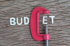 Finance, economy and business squeezing idea, wooden alphabet of. The word BUDGET using red clamp as G letter on wooden table, crisis and depression of company Royalty Free Stock Photos