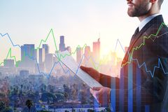 Finance and economy concept. Businessman holding document with digital forex chart on abstract city background. Finance and economy concept. Double exposure Stock Images