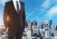 Finance and economy concept. Unrecognizable businessman on abstract city background with business chart. Finance and economy concept. Double exposure Royalty Free Stock Photography