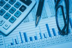 Finance, financial analysis, accounting accounts spreadsheet with pen glasses and calculator in blue. Close up concept for stock, Stock Photo