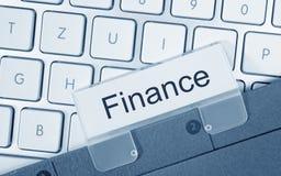 Finance - folder on computer keyboard stock photo