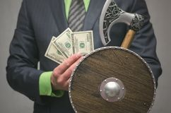 Finance insurance agent. Money deposite safety agent. Businessman holds in hand a toy viking axe weapon and shield. Life or finance insurance agent. Money Royalty Free Stock Photos