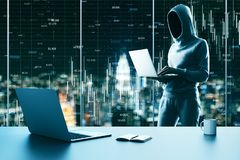Finance and malware concept. Hacker using laptop in modern office interior with supplies, coffee cup on desktop and night city view with forex chart. Finance and stock photo