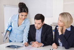 Finance manager sitting at desk talking together. Royalty Free Stock Image
