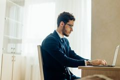 Finance market analyst in eyeglasses working at sunny office on laptop. Handsome businessman working with laptop in office royalty free stock photos