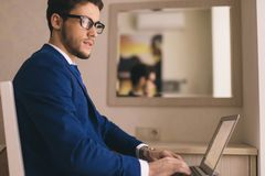 Finance market analyst in eyeglasses working at sunny office on laptop. Handsome businessman working with laptop in office stock image