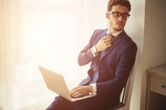 Finance market analyst in eyeglasses working at sunny office on laptop. Handsome businessman working with laptop in office royalty free stock image
