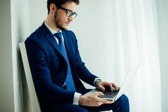 Handsome businessman working with laptop in office. Finance market analyst in eyeglasses working at sunny office on laptop while sitting at chair stock images