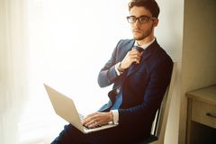 Handsome businessman working with laptop in office. Finance market analyst in eyeglasses working at sunny office on laptop while sitting at chair stock photo