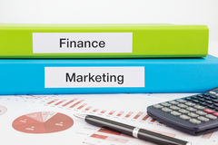Finance and marketing documents with reports. Finance and Marketing  words on labels with document binders, graphs and business reports Royalty Free Stock Images
