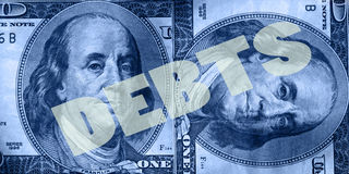 Finance and money series. Blue tinted image of  U.S. one hundred dollar bills and the word DEBTS placed over Benjamin Franklin's portrait Royalty Free Stock Photography